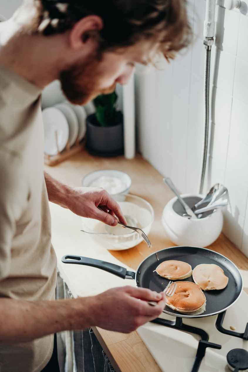 man cooking breakfast holding fork